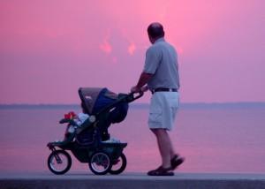 Padre paseando con su bebe atardecer en la playa