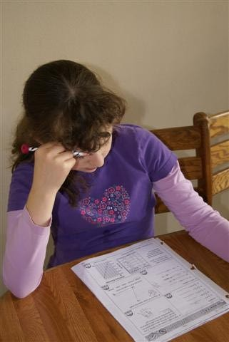 Niña haciendo los deberes sin la compañía de sus padres