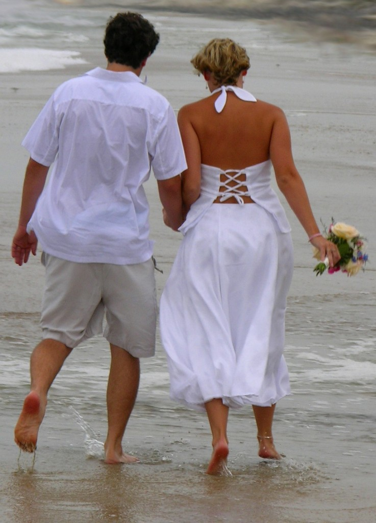 Pareja de recién casados paseando por la orilla del mar
